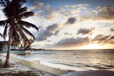 A peaceful sunset is welcomed by a calm oceans edge scene in Nassau Bahamas Stock Photo