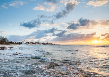Waves gently cover the beach in this view of the shoreline at sunset