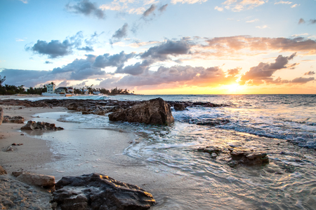 Rocks on the beach are displayed at low tide in this view of the shoreline at sunset in the Bahamas