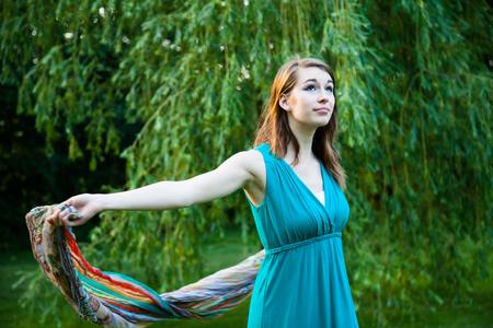 La muchacha hermosa está girando lentamente alrededor delante de un sauce. Despreocupado, feliz y alegre en un parque durante el verano.