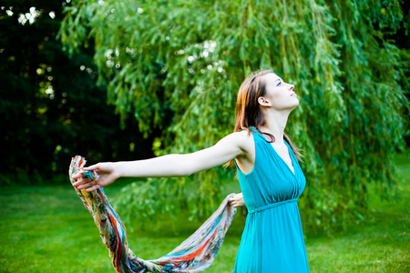 Beautiful girl is slowly spinning around in front of a willow tree. Carefree, happy and joyful in a park during summer.