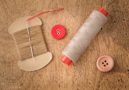 Vintage tools and accessories for sewing on wooden background