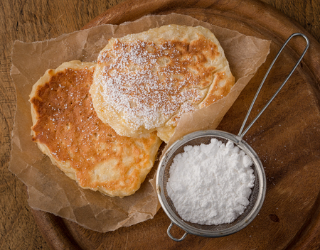 pancakes and strainer with powdered sugar