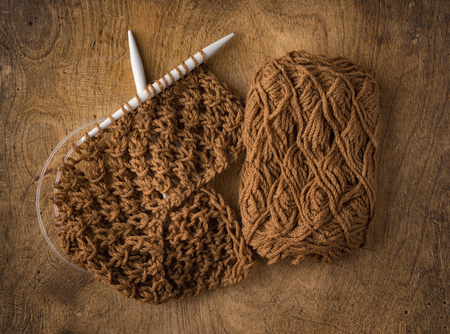 brown yarn, knitting needles and a piece of hand made cloth Stock Photo