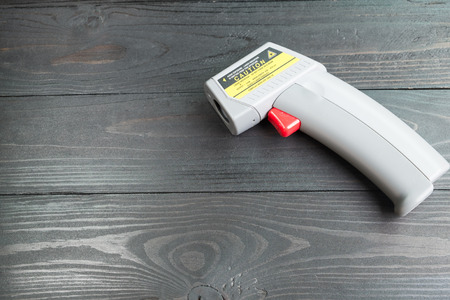 test equipment: non-contact Infrared thermometer for temperature measurement  on wooden background