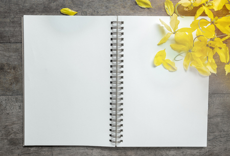 Notebook and flower on wooden background