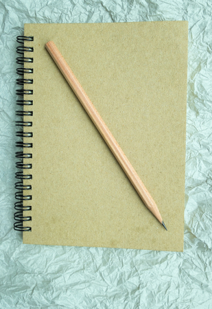 spiral binding: notebook and pencil on crumpled paper textured