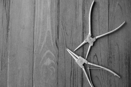 alicates: Pliers for remove the snap ring , Pliers on black wood