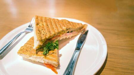 sanwich: Wheat bread sanwich with ham and cheese on plate, sandwich ham cheese garnished oregano