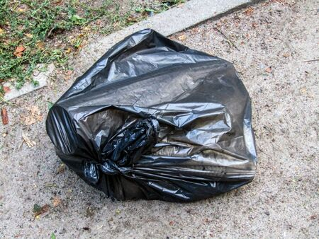 black garbage bag lying on the street. stock photo Stock Photo