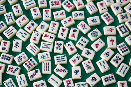 Mahjong tiles spread over green velvet canvas