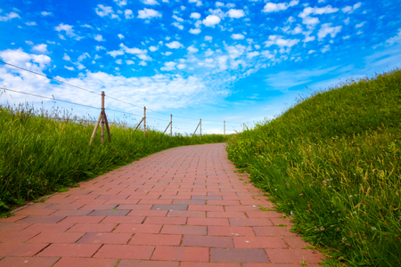 A path of red bricks leading across green grass fields and blue sky