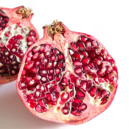 Two pieces of Pomegranate fruit on white background