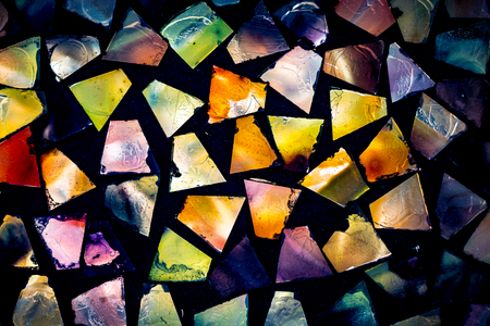 Pieces of colorful glass in dark mortar
