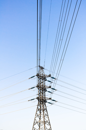 A steel electricity pylon with wires heading to three directions