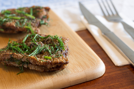 Two pieces of Herring steak on wooden serving board