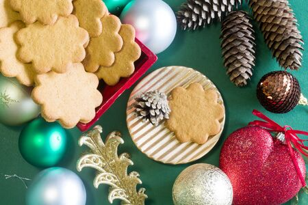 Various pieces of Christmas decorations on green background