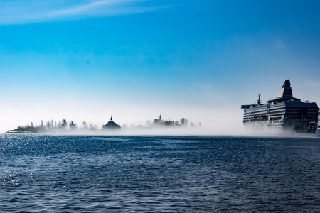 A ship and island in an isolated dense fog cloud on a clear day