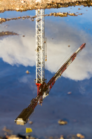 Reflection of a construction crane in a water puddle Imagens