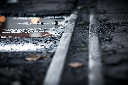 Closeup of an abandoned railroad track and water puddles