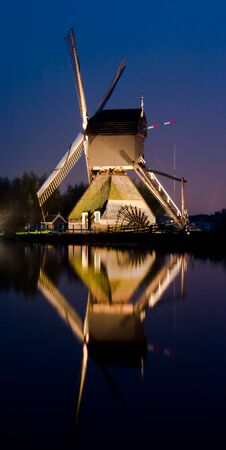 Single windmill shot at night with reflection in the water