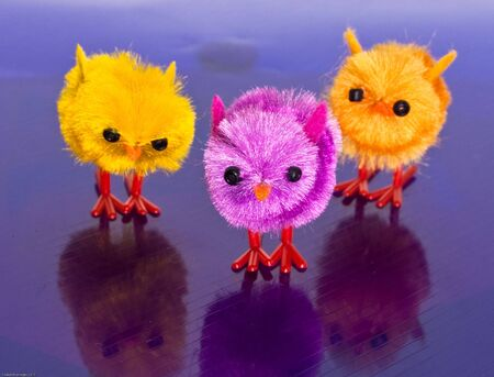 Orange and purple toy chicks on a striped surface Stock Photo