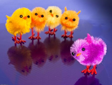 Orange, purple, pink, blue, yellow toy chicks on a striped surface