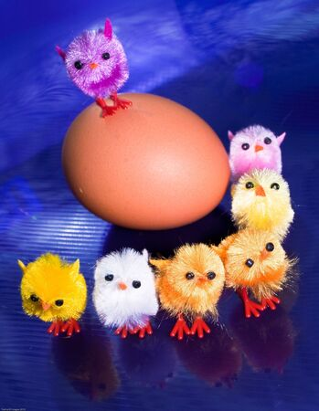 Toy orange and purple chicks in front of an egg
