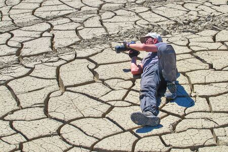 photographer lies on the ground cracked by the drought Stock Photo