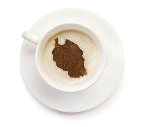 A cup of coffee with foam and powder in the shape of Tanzania.(series) photo