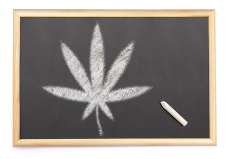 A blackboard with a chalk and the shape of the cannabis symbol drawn onto. (series) photo