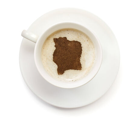 A cup of coffee with foam and powder in the shape of Ivory Coast.(series) photo