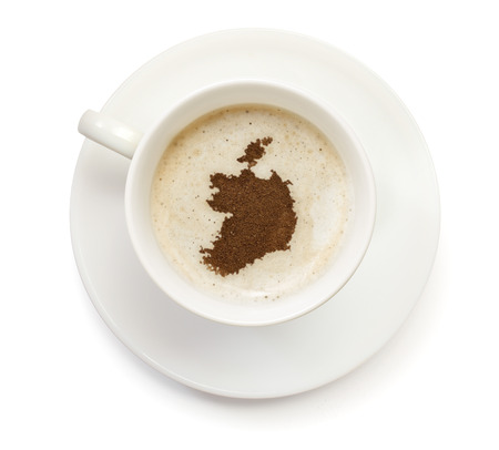 A cup of coffee with foam and powder in the shape of Ireland.(series) photo