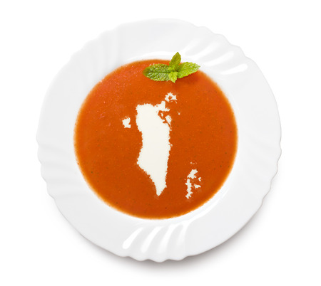 A plate tomato soup with cream in the shape of Bahrain.(series) photo