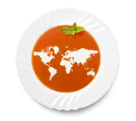 world map outline: A plate tomato soup with cream in the shape of World.(series) Stock Photo