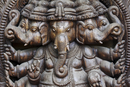 A detailed close up of multiple wodden Ganeshas in one statue