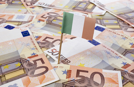 tax evasion: Flag of Ireland sticking in european banknotes.(series) Stock Photo