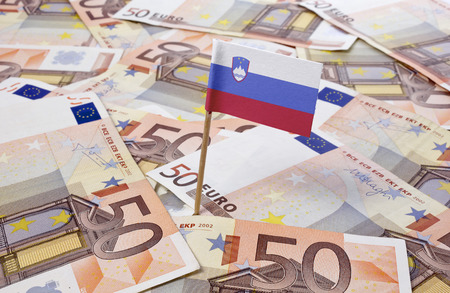 tax evasion: Flag of Slovenia sticking in european banknotes.(series) Stock Photo
