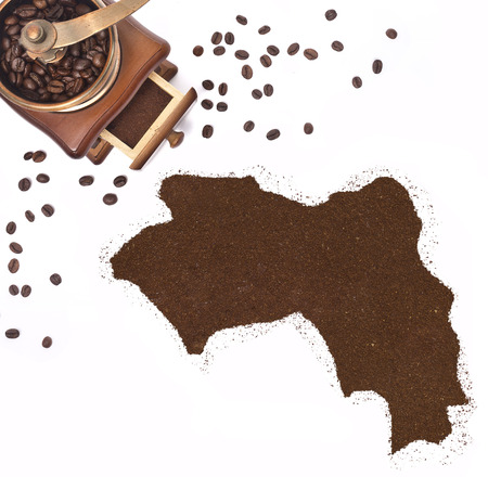 Coffee powder in the shape of Guinea and a decorative coffee mill.(series) photo