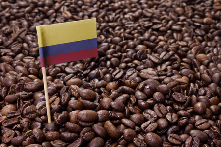 Flag of Colombia sticking in roasted coffee beans.(series)