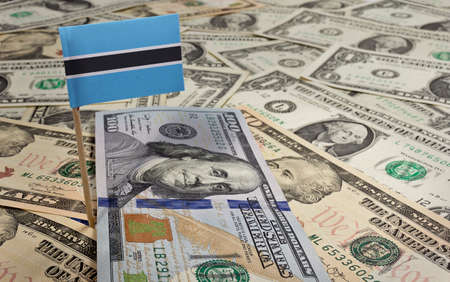 botswanan: Flag of Botswana sticking in a variety of american banknotes.(series) Stock Photo