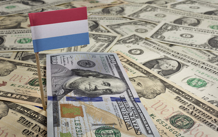 Flag of Luxembourg sticking in a variety of american banknotes.(series) photo