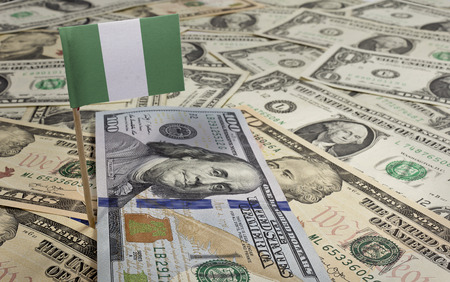 Flag of Nigeria sticking in a variety of american banknotes.(series)