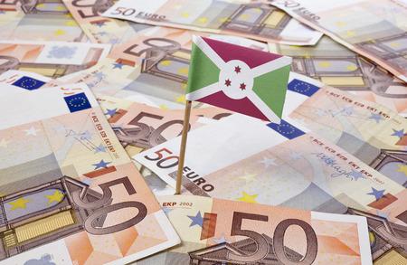 burundi: Flag of Burundi sticking in european banknotes.(series) Stock Photo