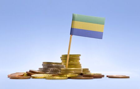economizing: Flag of Gabon in a mixed stack of european coins and a blue background.(series)