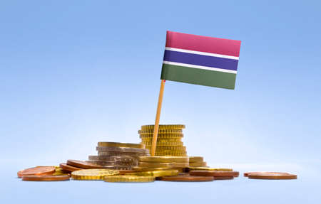 economizing: Flag of Gambia in a mixed stack of european coins and a blue background.(series) Stock Photo