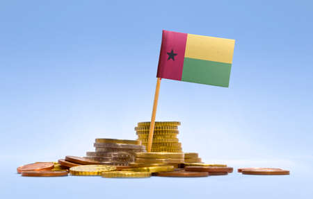 economizing: Flag of Guinea-Bissau in a mixed stack of european coins and a blue background.(series)