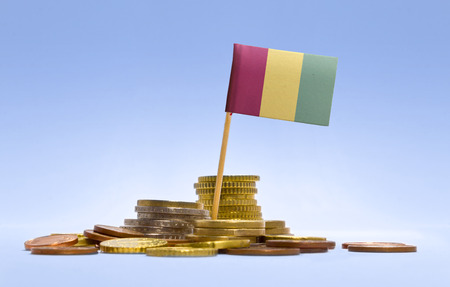 economizing: Flag of Guinea in a mixed stack of european coins and a blue background.(series)
