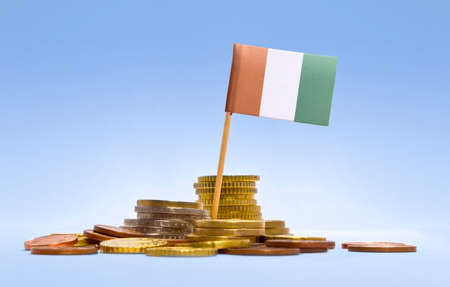 economizing: Flag of Ivory Coast in a mixed stack of european coins and a blue background.(series)