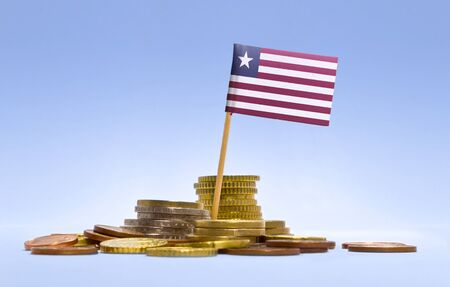 economizing: Flag of Liberia in a mixed stack of european coins and a blue background.(series) Stock Photo